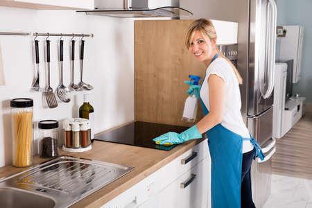 젊은 웃는 청소 서비스 여자 부엌에서 더러운 유도 스토브 청소 스톡 콘텐츠