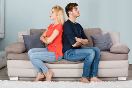 Young Sad Couple In Fight With Arms Crossed Sitting On Sofa After Quarrel At Home Stock Photo