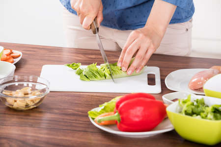 Close-up Of Young Woman Hand Cutting Vegetable On Chopping Board While Cooking In Kitchen