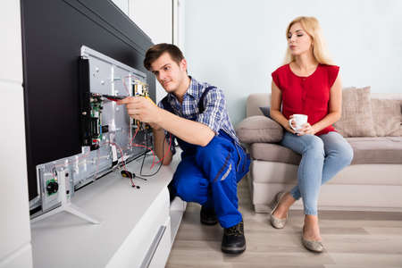 lcd tv: Young Woman Sitting On Couch Looking At Male Technician Repairing TV At Home Stock Photo