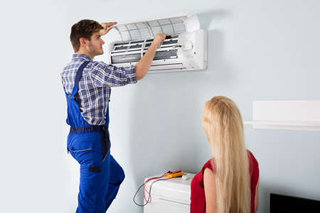 Woman Looking At Young Male Technician Repairing Air Conditioner At Home