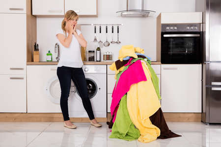 untidy: Exhausted Young Woman Standing Near Pile Of Untidy Clothes In Kitchen