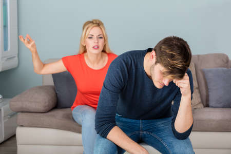 divorcing: Depressed Divorcing Woman Sitting On Couch Having Argument With Man About Infidelity At Home