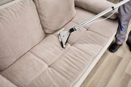 High Angle View Of A Person Cleaning Sofa With Vacuum Cleaner Stock Photo