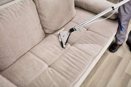 Hoge hoekmening van een persoon schoonmaak sofa met stofzuiger