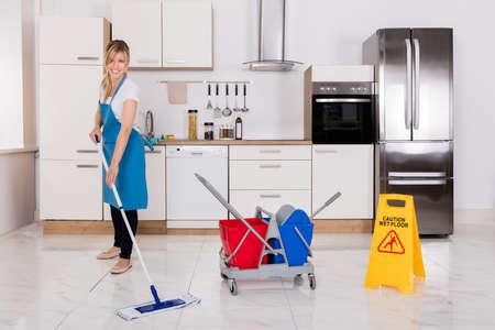 Schoonmaakservice Maid met mop om de keukenvloer te reinigen