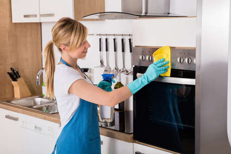 apartment cleaning: Young Housemaid Service Woman Cleaning Microwave Oven With Spray Bottle And Rag