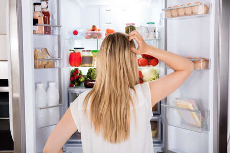 refrigerator: Rear View Of Young Woman Looking In Fridge At Kitchen