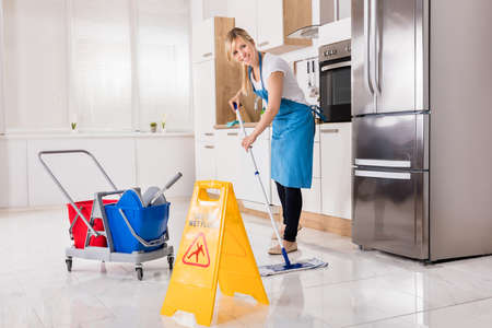 Cleaning Service Woman Using Mop To Clean Kitchen Floor Photo