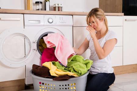 Mujer joven que mira la ropa maloliente fuera de la lavadora en la cocina