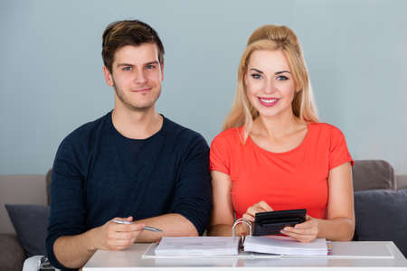 young happy couple: Smiling Couple Calculating Invoice Using Calculator To Plan Family Budget And Save Money At Home