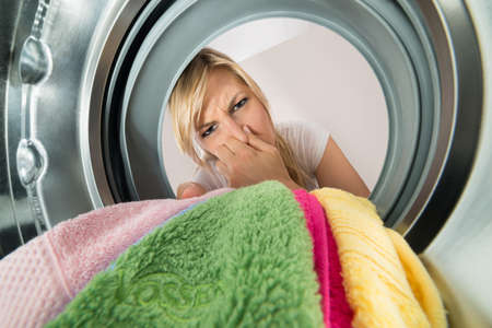 stinky: Close-up Of Young Woman Inserting Stinky Clothes In Washing Machine