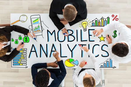 high angle view: High Angle View Of Businesspeople Drawing The Mobile Analytic On Office Desk In Office