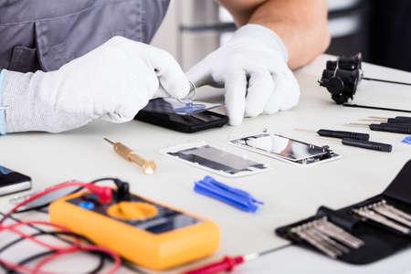 携帯電話を修正手袋を身に着けている技術者の手のクローズ アップ 写真素材