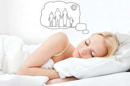 Young Woman Dreaming Of Having Family Together While Sleeping On Bed photo
