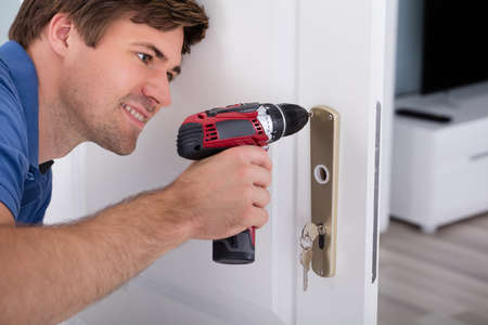 overalls: Close-up Of Smiling Happy Young Male Installing Door Lock On Door Using Wireless Screwdriver