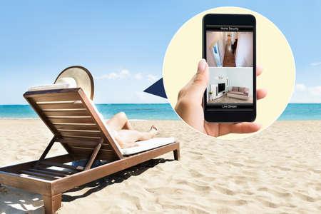 Mujer que se relaja en silla de salón en la playa Mirando a la Sistema de seguridad en el teléfono móvil