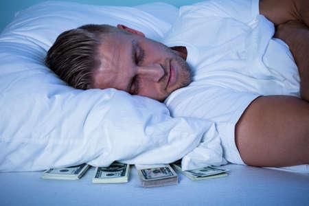 ベッドの上の彼の枕の下保管紙幣で眠っている男のクローズ アップ