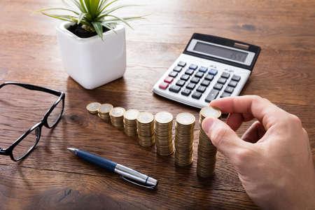 Die Berechnung Nahaufnahme einer Person Hand auf Holz-Schreibtisch vor Gestapelte Münzen. Einkommenssteuer anheben Konzept