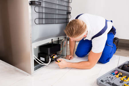 Young Male Technician Checking Refrigerator With Screwdriver Stock Photo