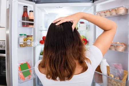 refrigerator with food: Rear View Of Confused Woman Searching For Food In The Fridge