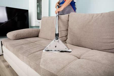 Trabajador masculino de los jóvenes de limpieza en el sofá con la aspiradora