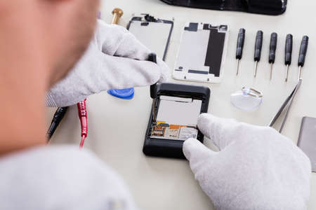 Primer De La Persona Fijación Celular roto con destornillador Foto de archivo