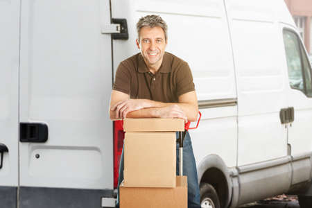 Smiling Delivery Man Or Mover Leaning On Cardboxes In Front Of The Van photo