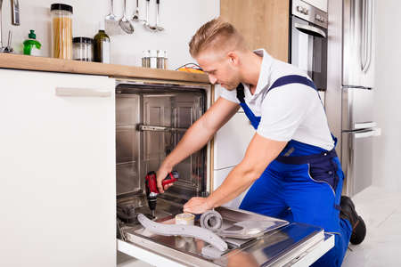 Young Repairman Fixing Dishwasher With Electric Drill