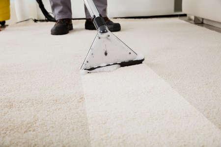 掃除機でのカーペットの掃除人のクローズ アップ