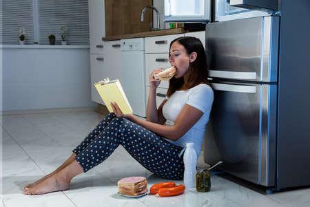 comida chatarra: Mujer joven del libro de lectura mientras que come el emparedado en cocina