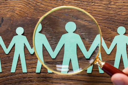 High Angle View Of Person Hand Using Magnifying Glass On Cut-out Figures On Wooden Desk Stock Photo