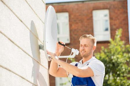 Lachende Jonge Man Installeren TV Satelliet Schotel Aan Muur