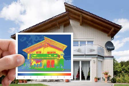 Persona della holding della mano infrarossa Thermovision Immagine Mostrando la mancanza di isolamento termico all'esterno della casa Archivio Fotografico - 70448742