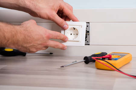 Close-up Of Persons Hand Installing Socket On Wall At Home