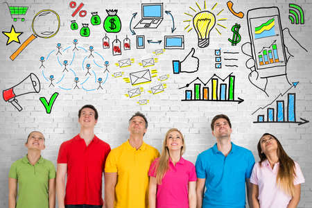 Group Of People Looking Up At Digital Marketing Concept On Brick Wall Stock Photo