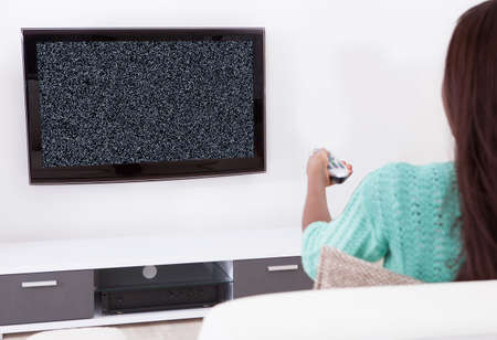 no signal: Woman Sitting On Couch With Remote Control Watching Television Showing No Signal Stock Photo