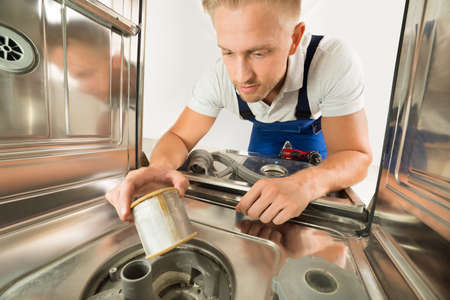 servicing: Young Man In Overall Repairing Dishwasher In Kitchen Stock Photo
