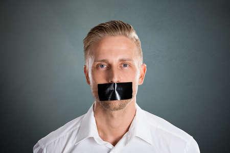 Jeune homme avec un ruban adhésif noir sur sa bouche contre un fond gris Banque d'images