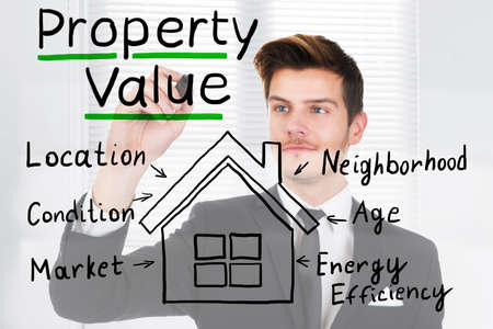 A Successful Businessman Drawing The Concept Of Property Value On Transparent Glass In Office