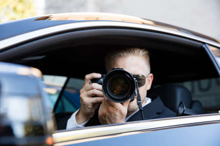 Man Sitting Inside Car Photographing With SLR Camera Foto de archivo