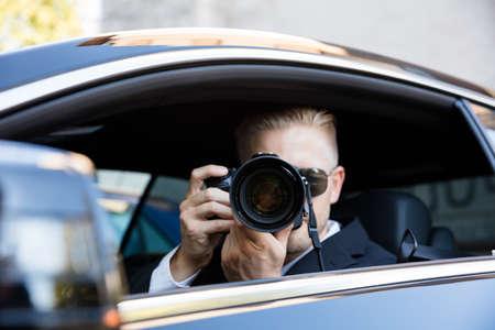 Uomo che si siede dentro l'automobile che fotografa con la macchina fotografica reflex