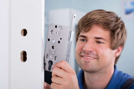 Close-up Of Mans Hand Installing Door Lock At Home