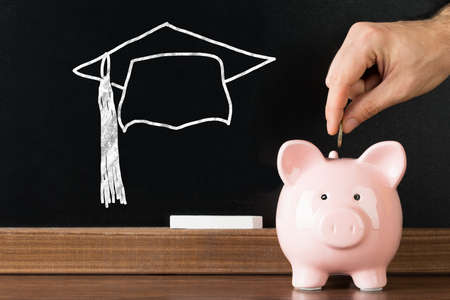 inserting: Person Hand Inserting Coin In Piggybank With Graduation Cap Drawn On Blackboard At Background
