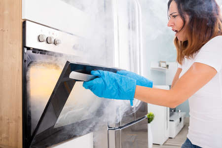 Young Unhappy Woman Opening Door Of Oven With Full Of Smoke Stockfoto