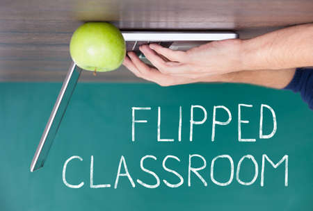 flipped: Flipped Classroom Concept On Blackboard With Person Using Laptop