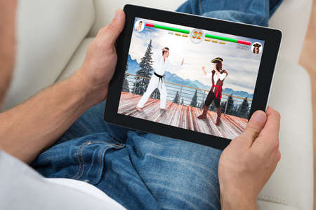 digital tablet: High Angle View Of Man Playing Videogame On Digital Tablet At Home Stock Photo