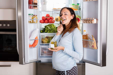 pregnant women donuts: Young Pregnant Woman Enjoy Eating Jar Of Pickle In Front Of Open Refrigerator In Kitchen Stock Photo