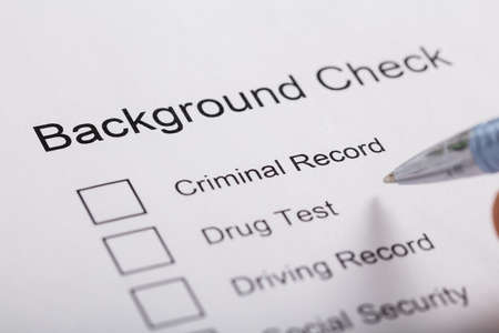 criminal activity: Close-up Of Pen Over Background Check Form Stock Photo