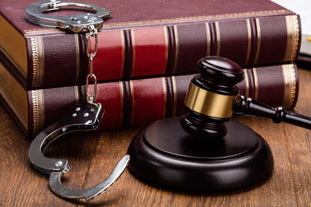 Gavel And Handcuffs With Red Legal Book On Wooden Table Stock Photo